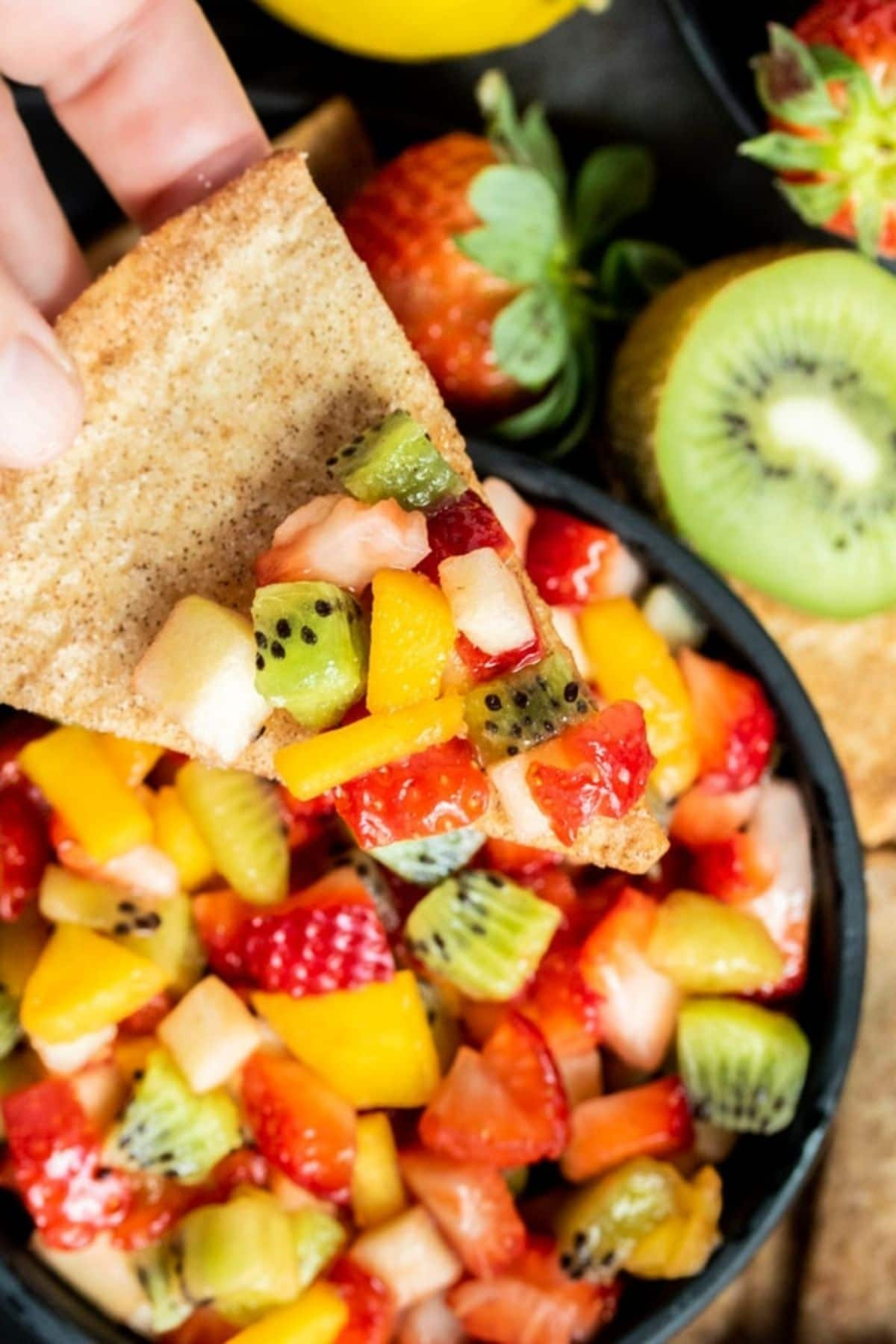 Chip dipping into fruit salsa in black bowl