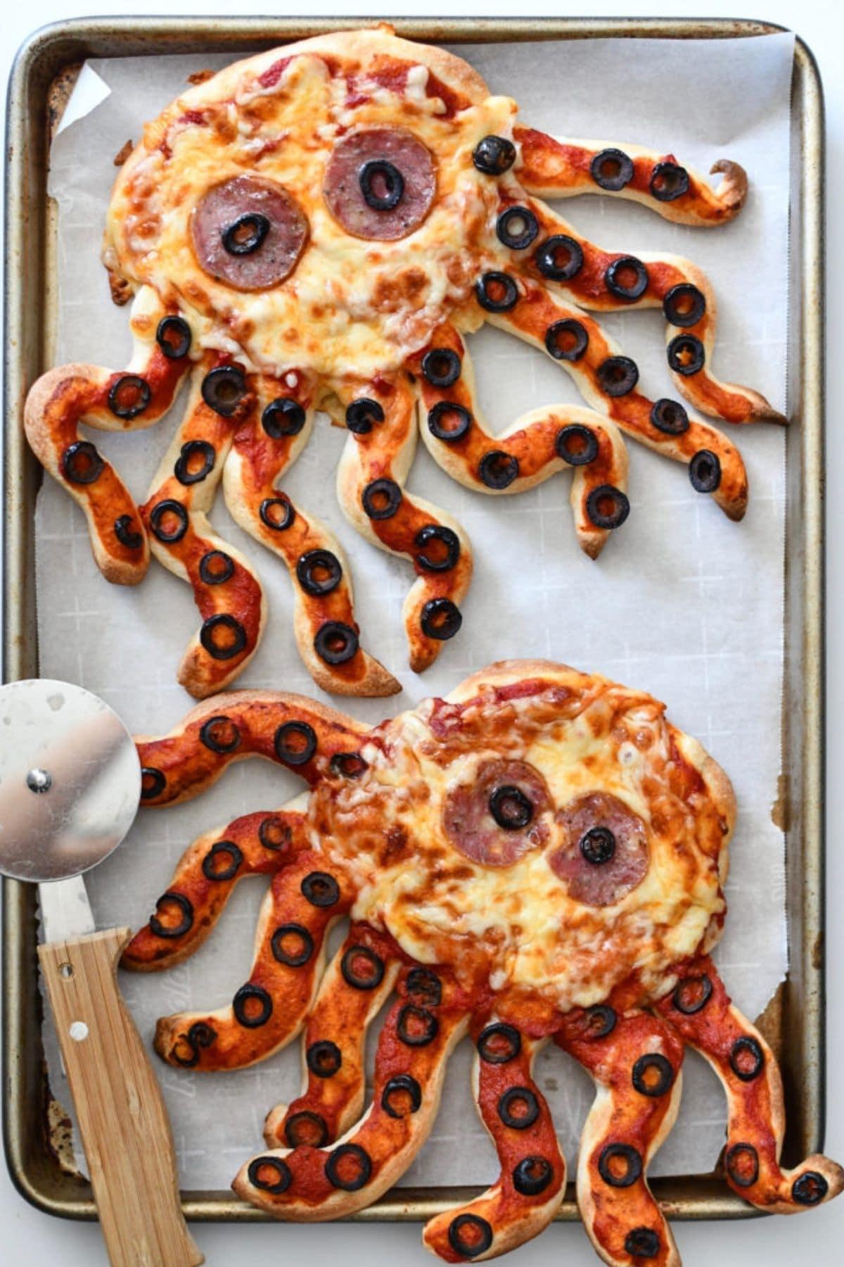 Octopus shaped pizzas on baking sheet