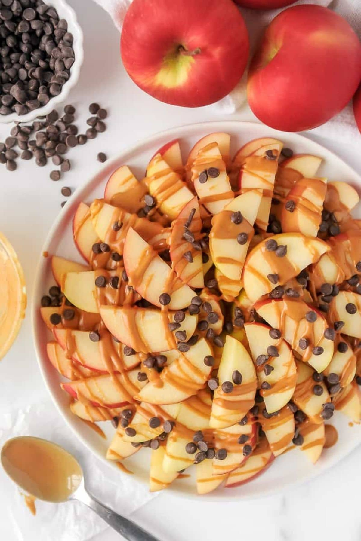 Apple nachos on white plate with mini chocolate chips