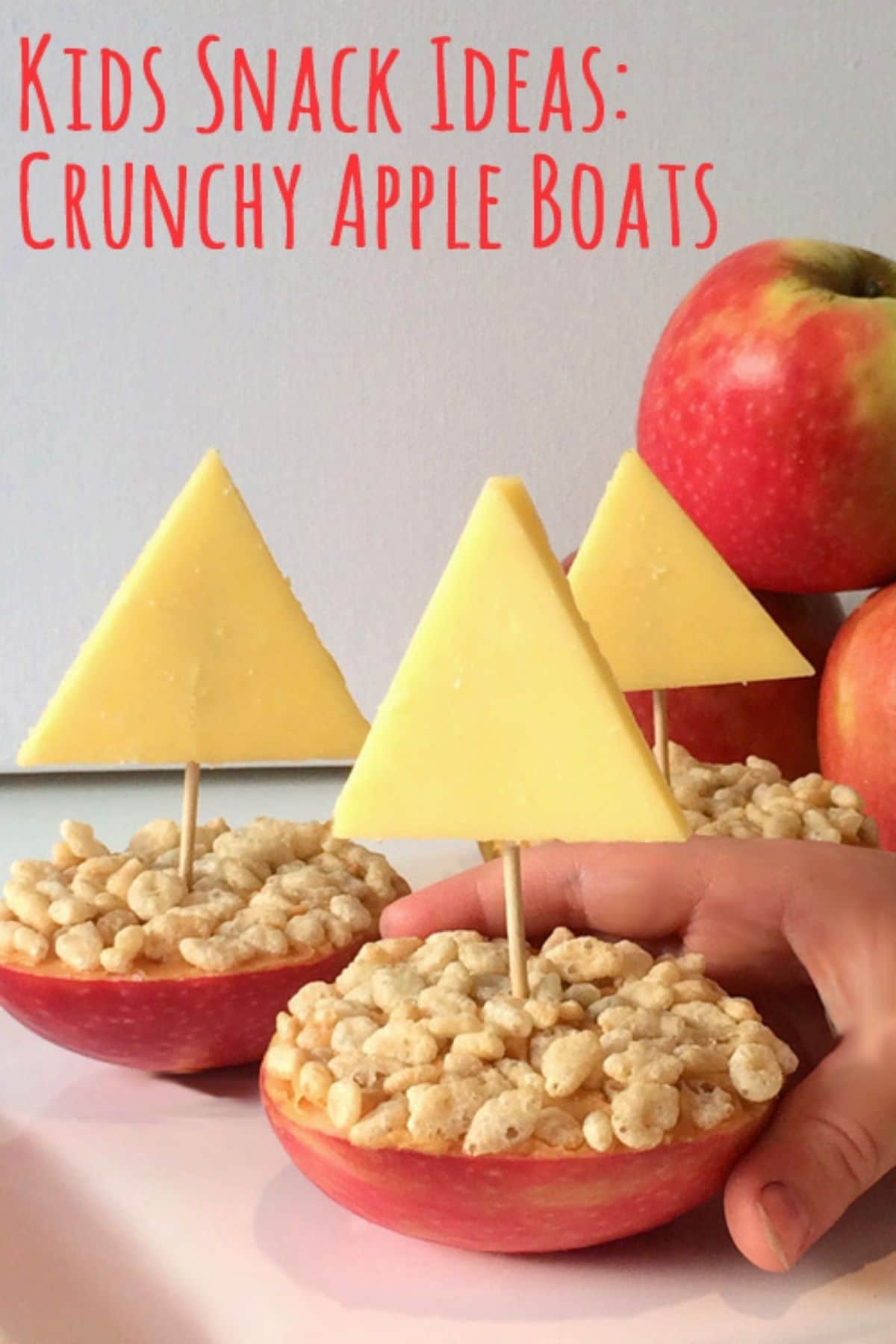 Apple halves stopped with peanut butter rice cereal and a triangle of cheese