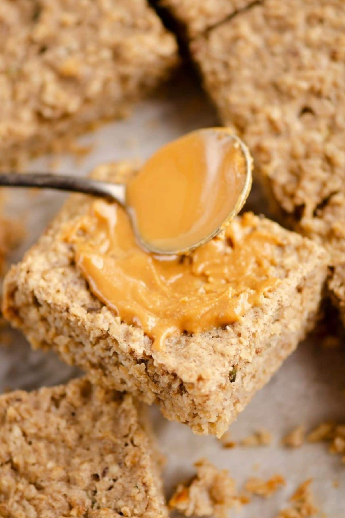 Spreading a spoon of peanut butter onto square oatmeal bar