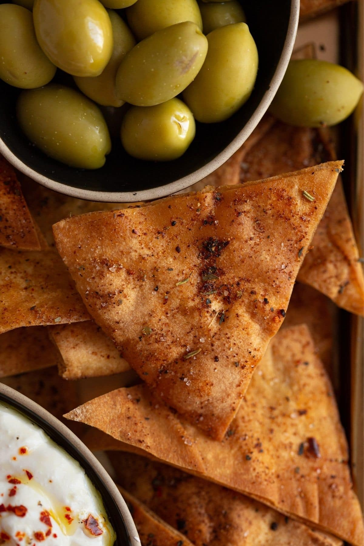 Seasoned pita chips on tray by bowl of green olives