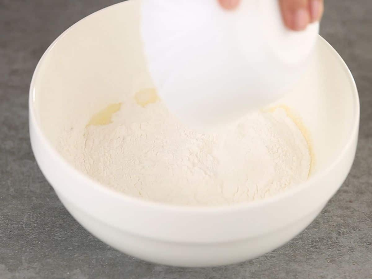 Pouring dry pudding into white bowl