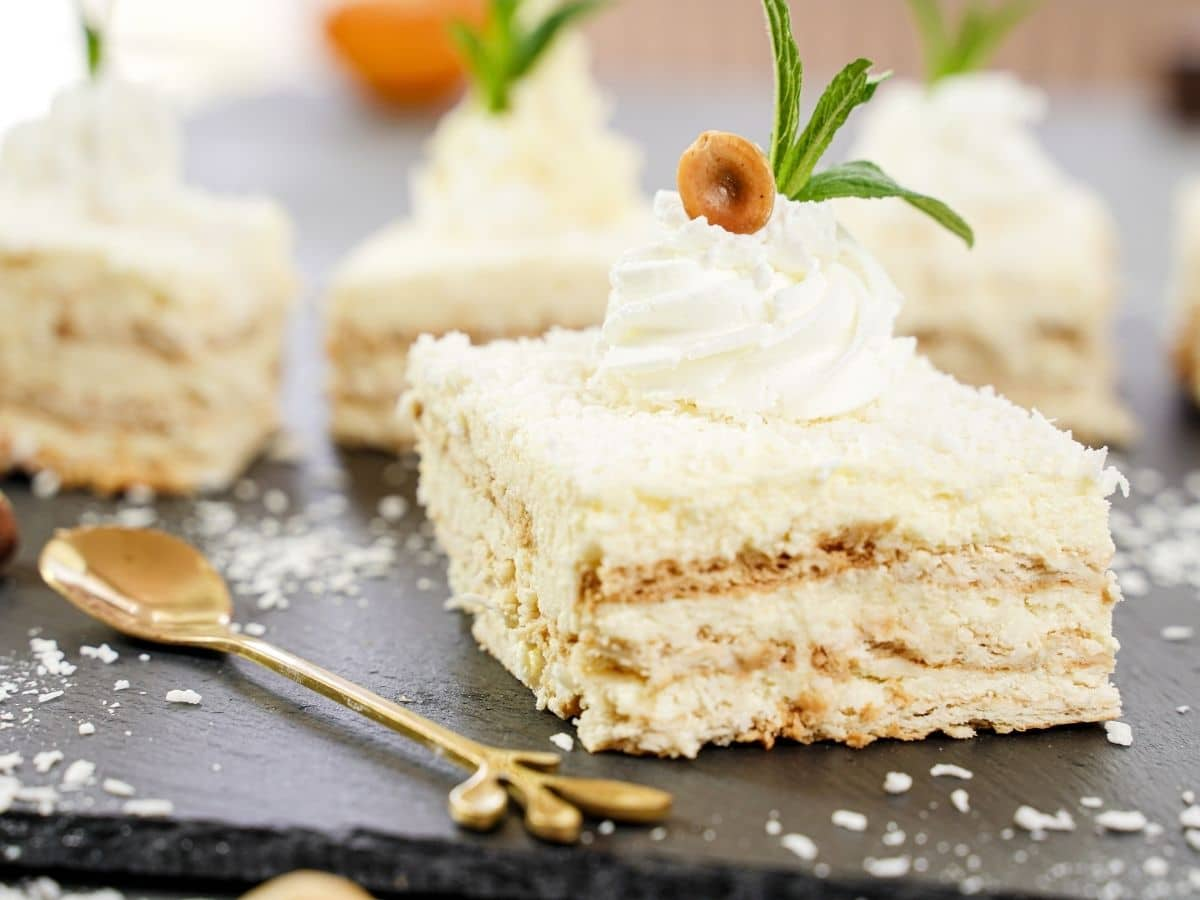 Square slices of coconut cake topped with whipped cream on black tray
