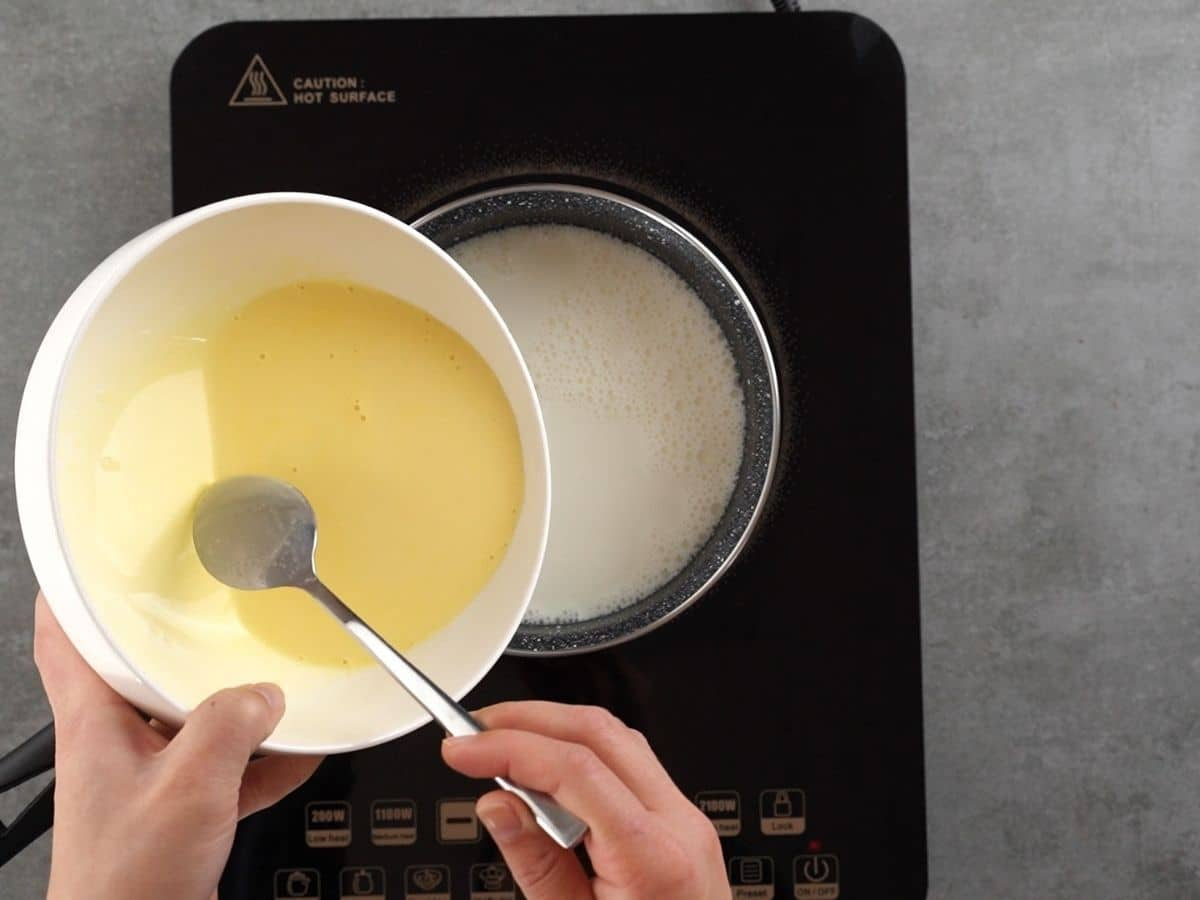 Pouring pudding into milk in saucepan