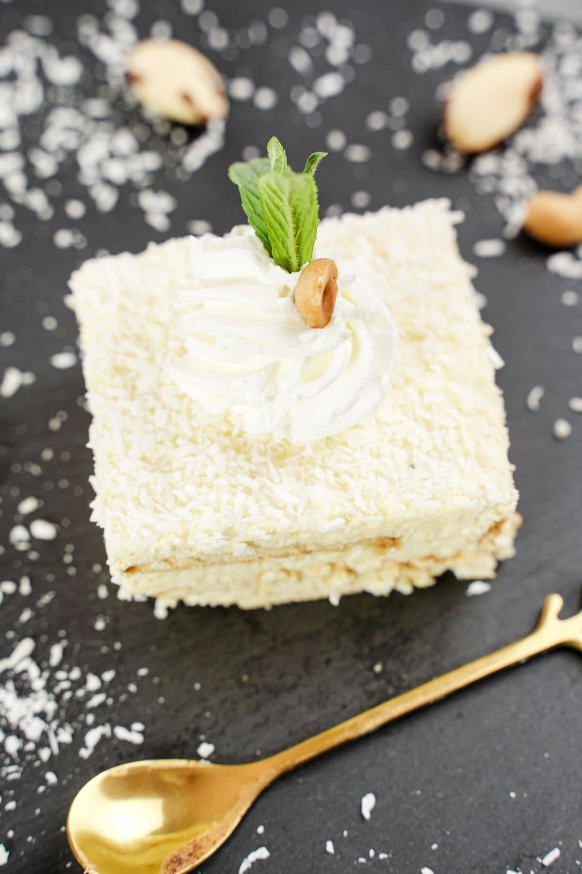 Single slice coconut cake on black tble with mint sprig on top