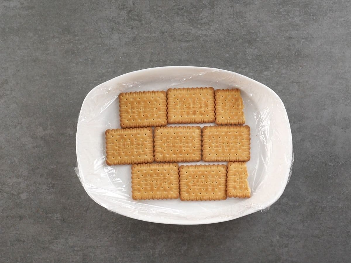 White oblong dish with layer of digestive biscuits