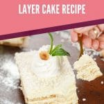 Coconut cake with mint and cream on top on black table with pink banner saying no bake coconut layer cake recipe
