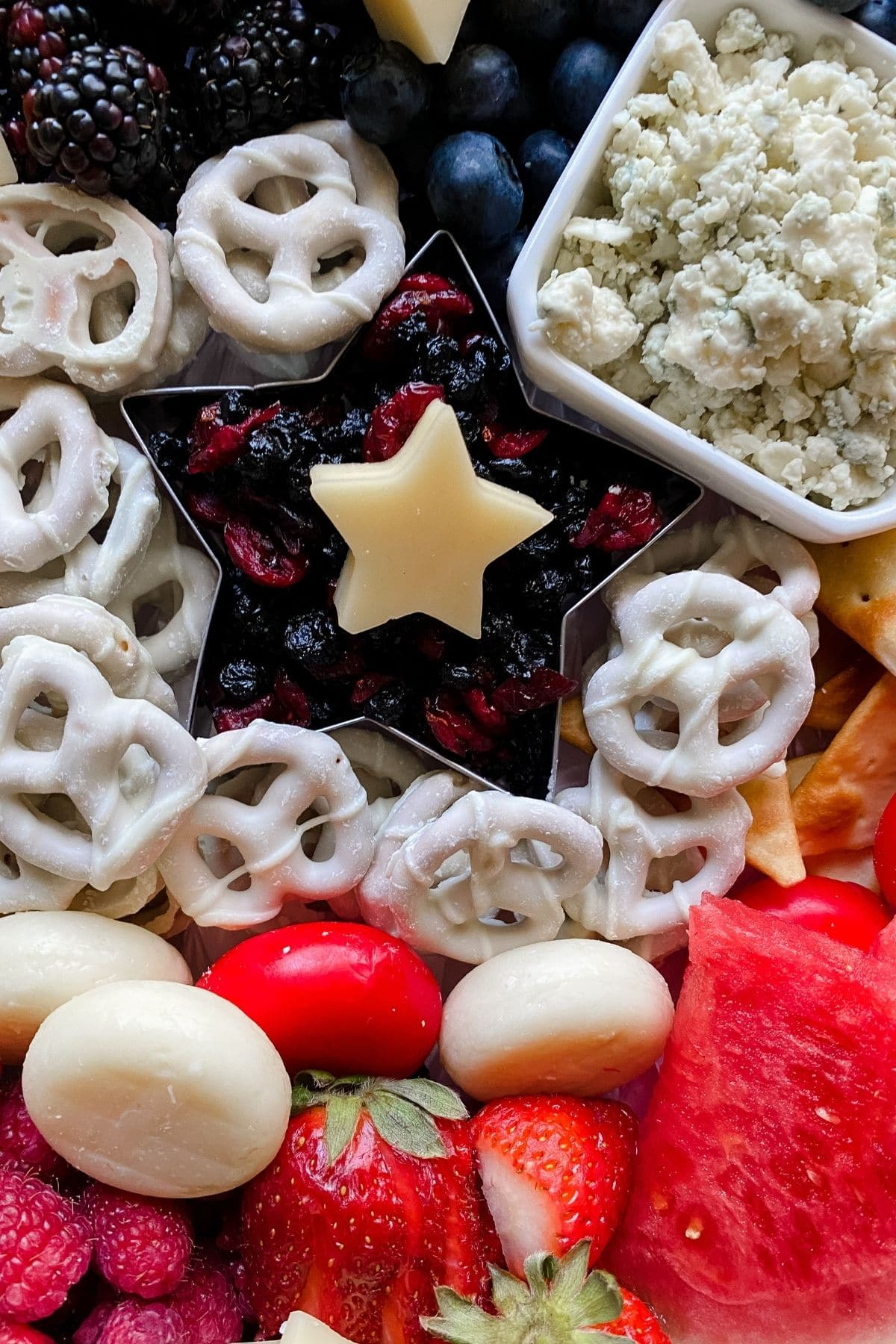 Cheese in star shape on top of dried berries in star cookie cutter