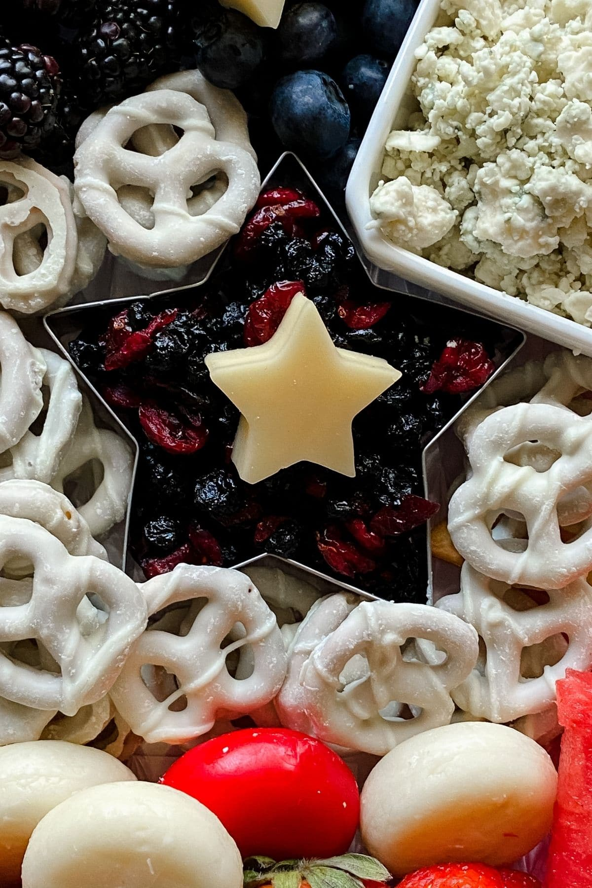Star cookie cutter holding dried berries with cheese star on top