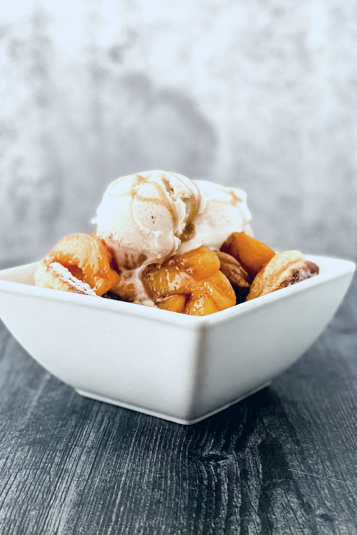 White square bowl on gray wood with peach cobbler and ice cream on top
