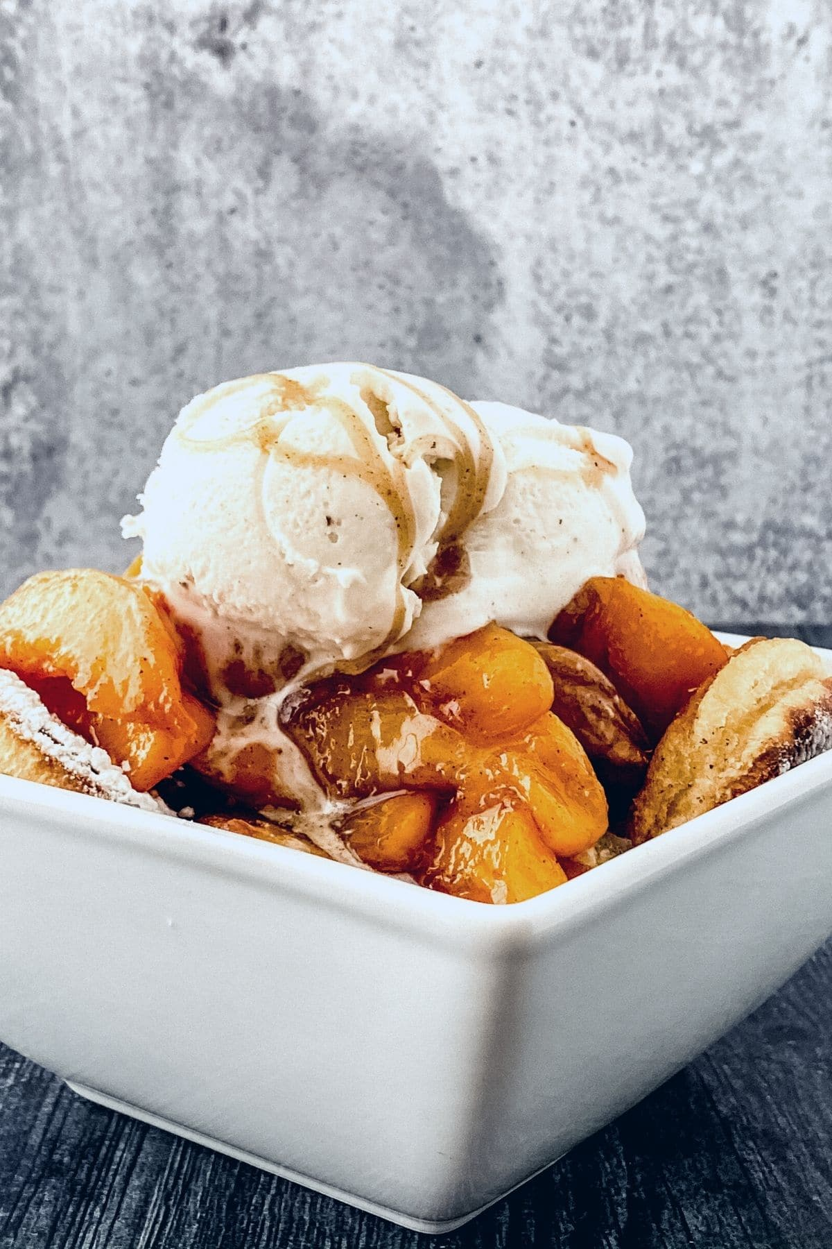 White square bowl with peach cobbler and ice cream on gray counter