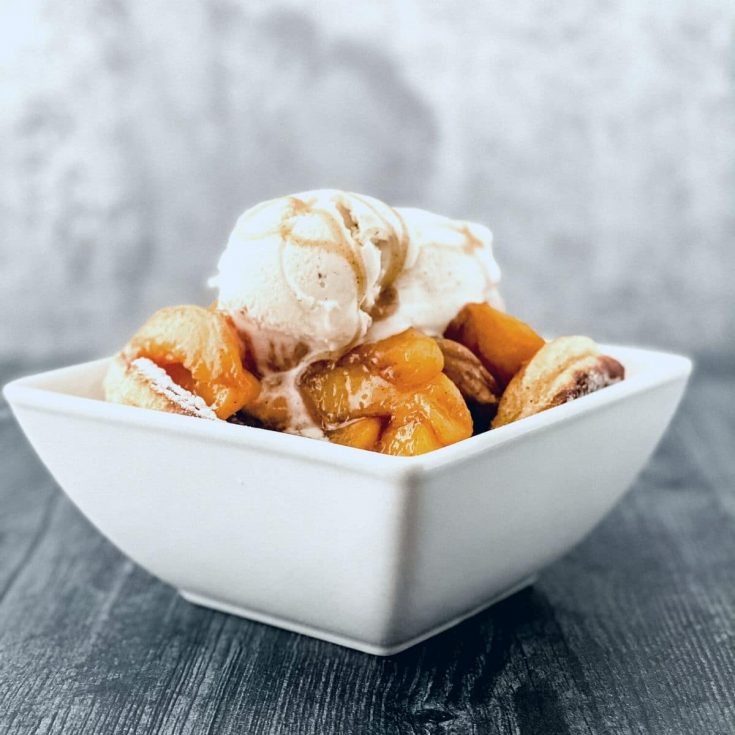 Square white bowl with peaches and ice cream on gray table
