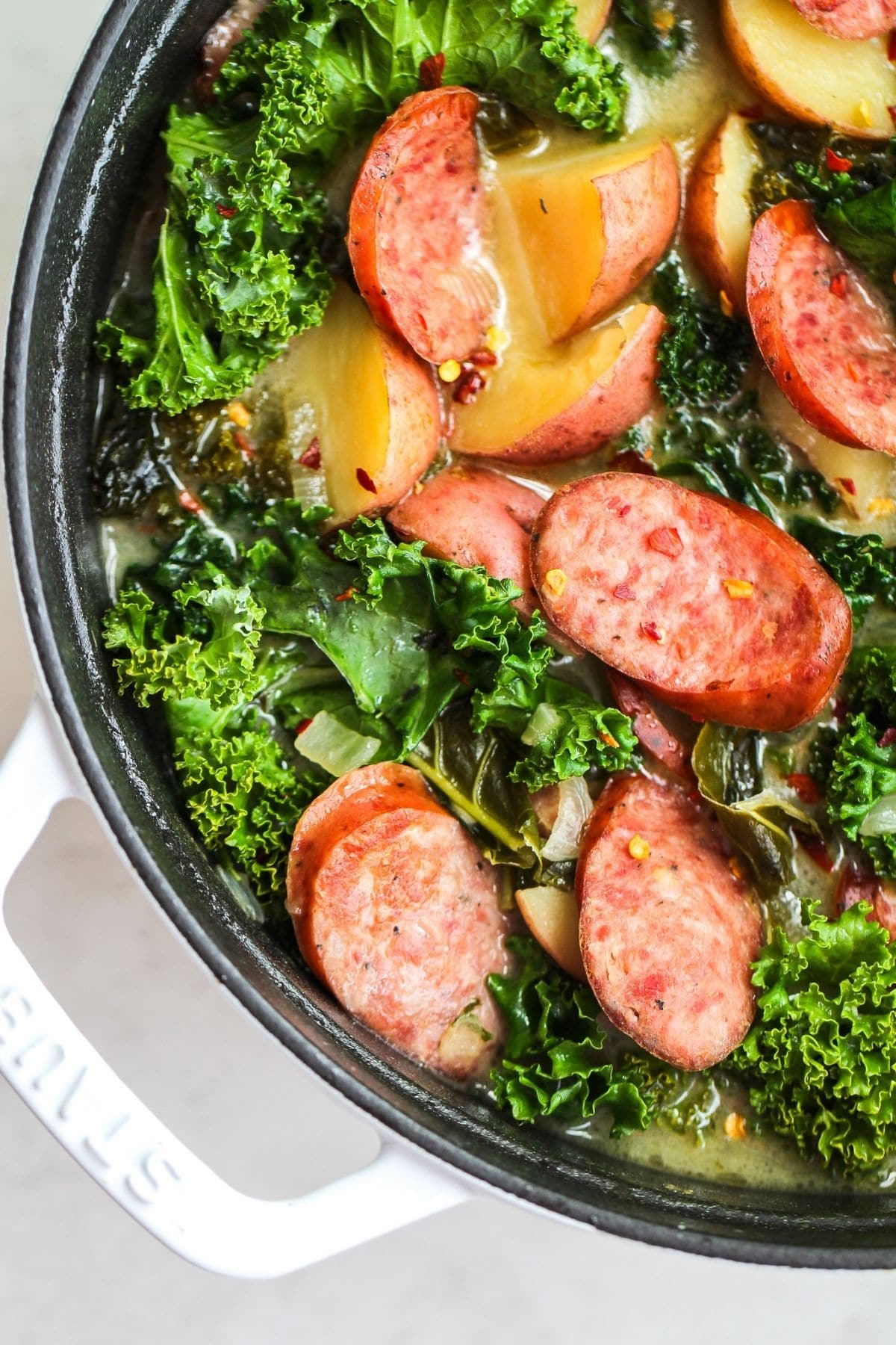 Kale and potatoes in black bowl with sausage