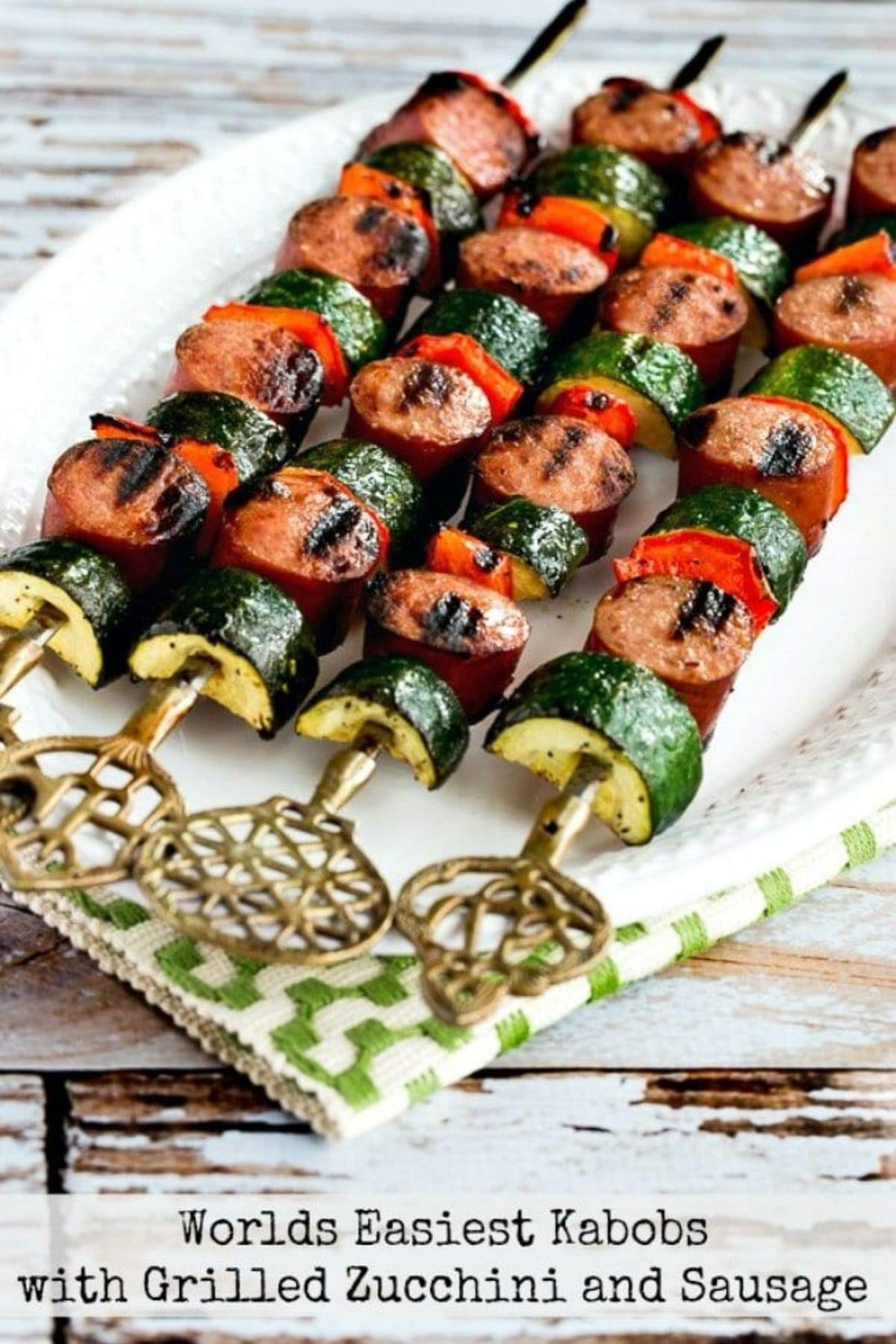 Kabobs with sausage and zucchini on white plate