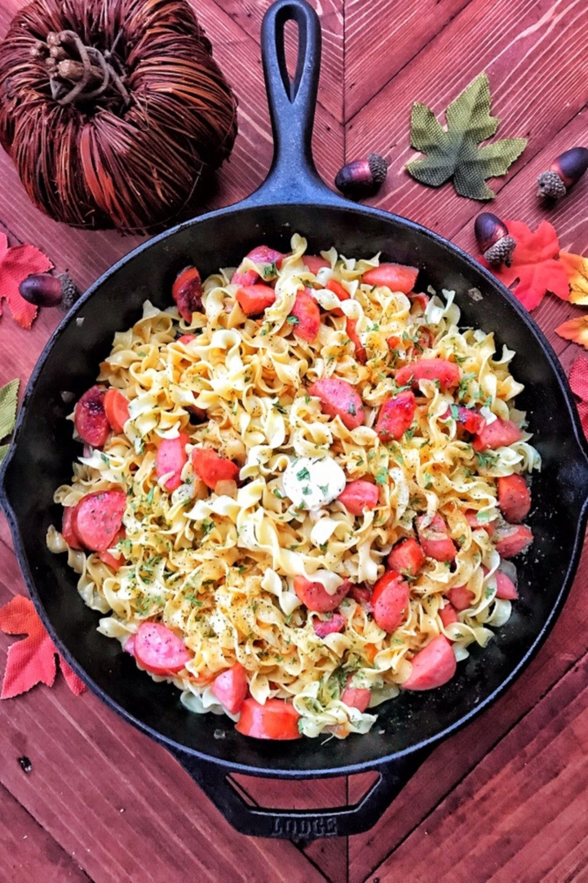 Cast iron skillet with sausage and egg noodles on red table