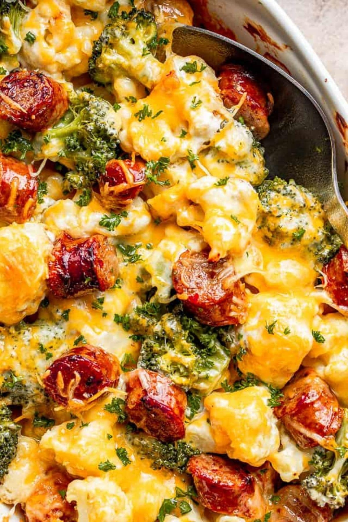 Sausage cauliflower and broccoli in bowl topped with cheese