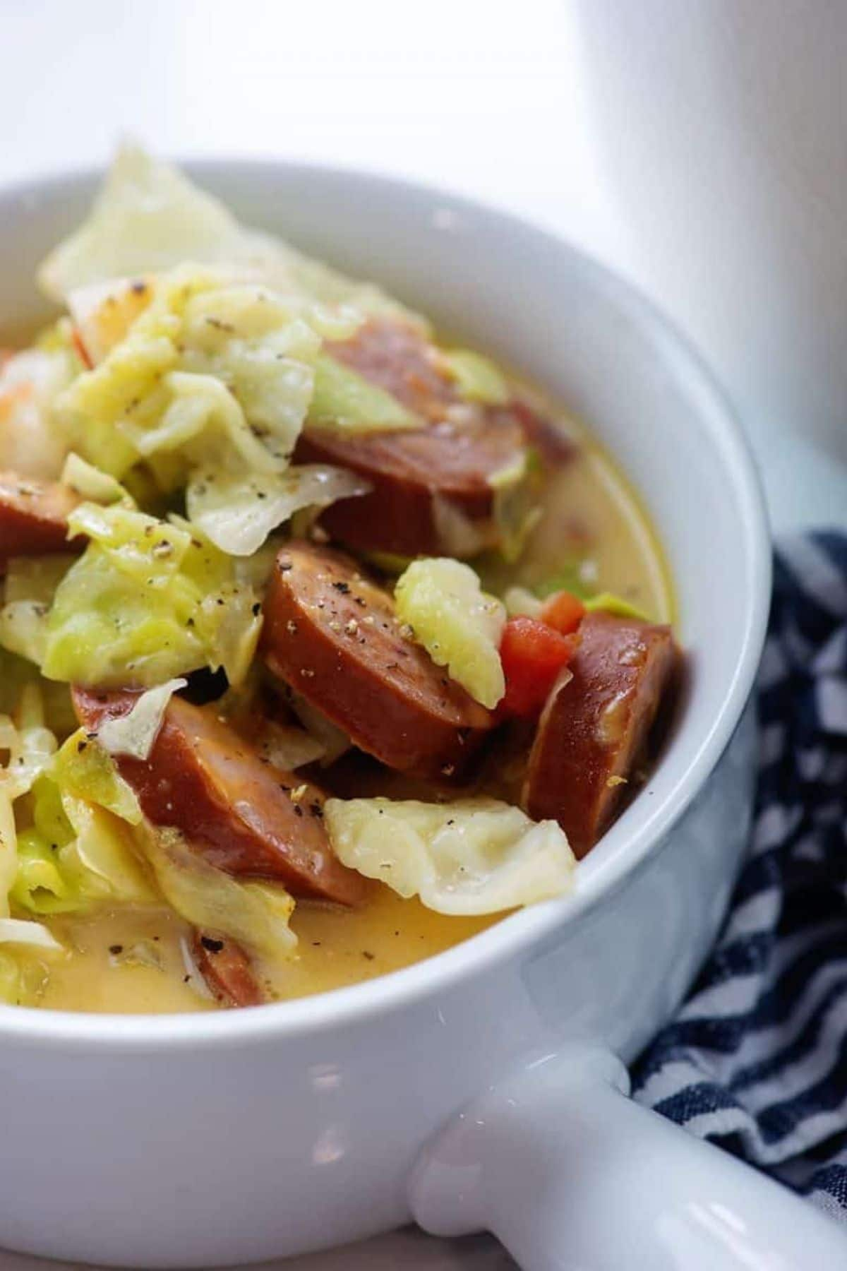 White bowl of cabbage and sausage