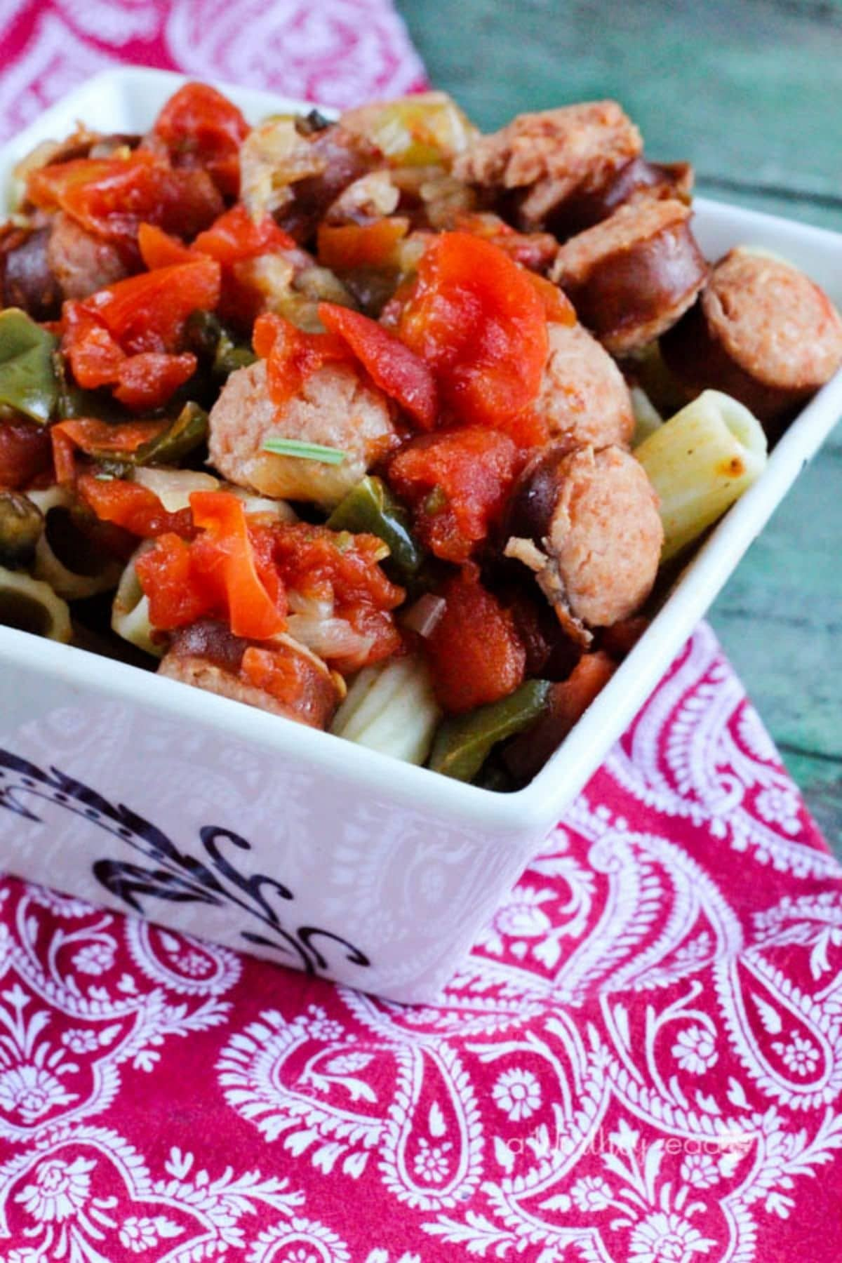 White square bowl on pink floral napkin with sausage and peppers