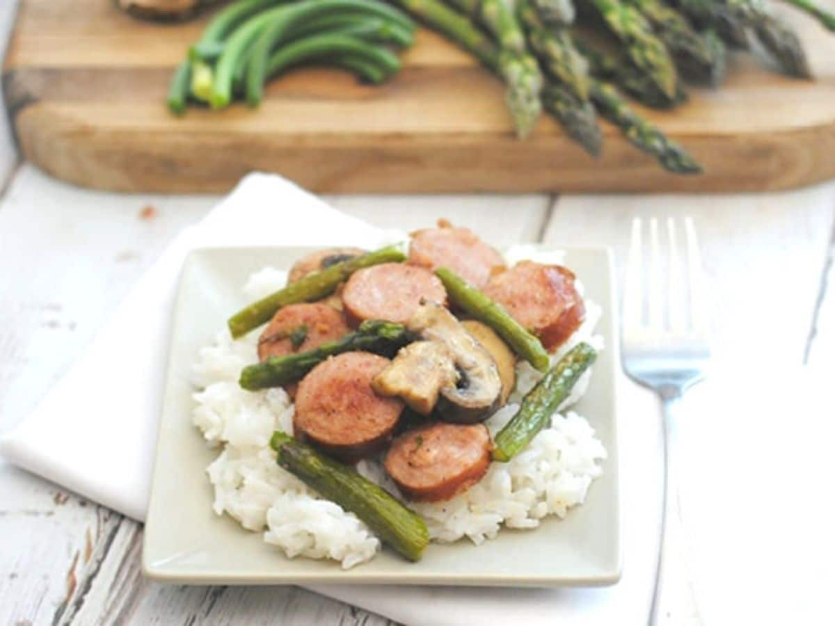 White plate with rice sausage and asparagus