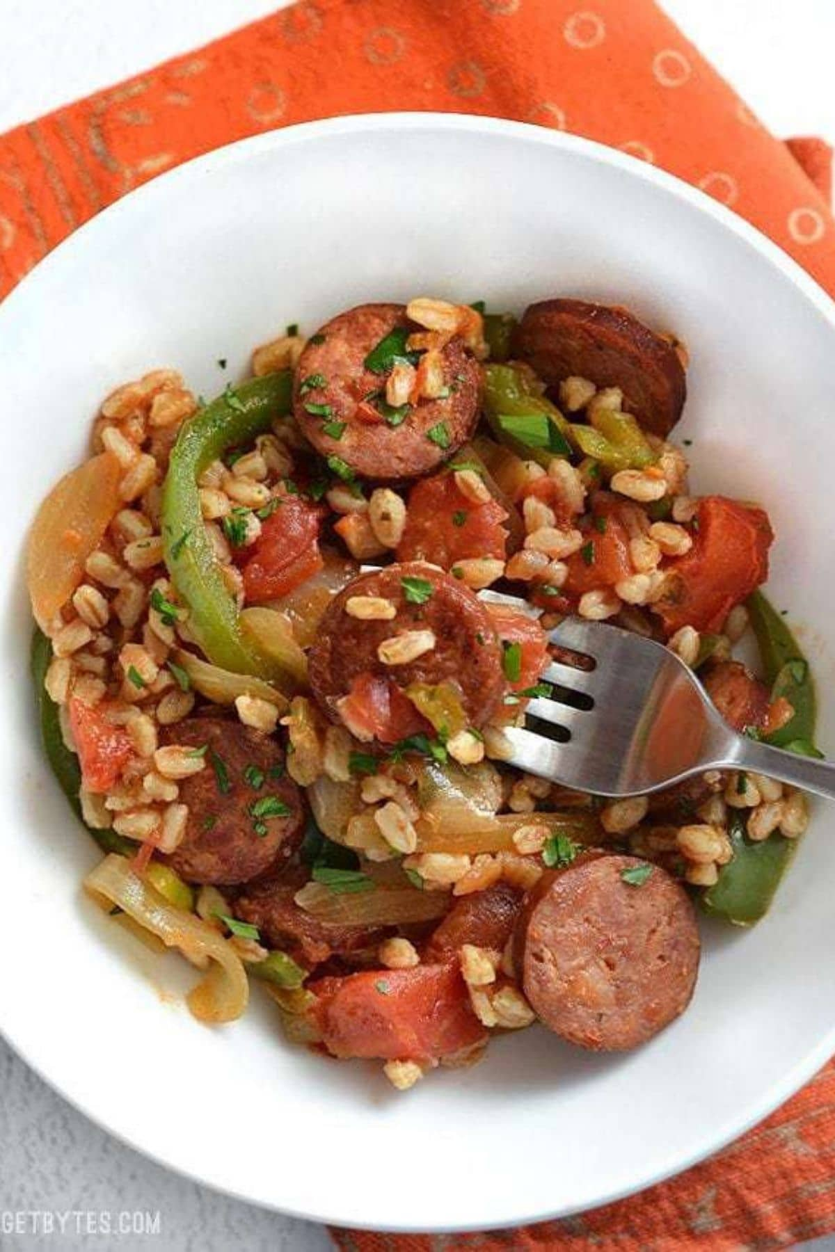 Sausage and peppers in white bowl with farro