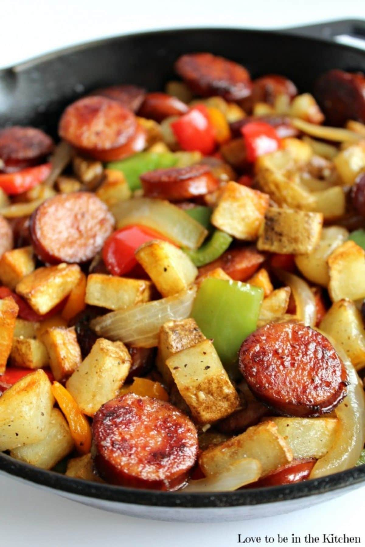 Peppers onions potatoes and sausage up close in cast iron skillet