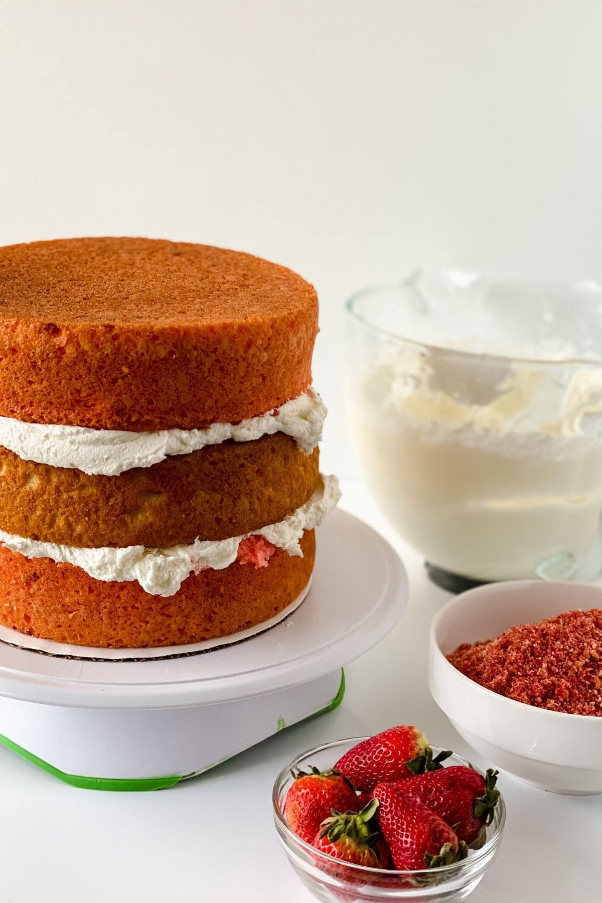 Three layer cake on white cake stand with frosting between layers