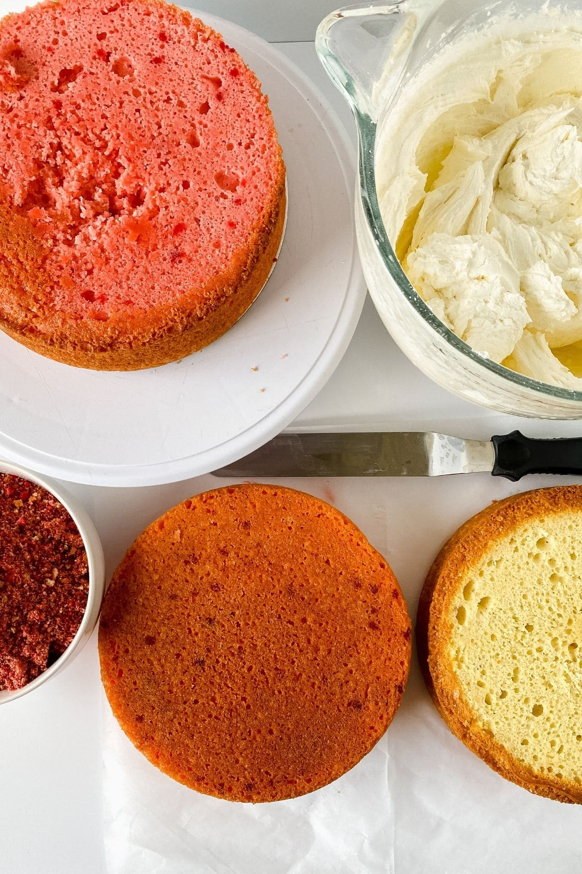 Cakes and frosting lined up to layer on table