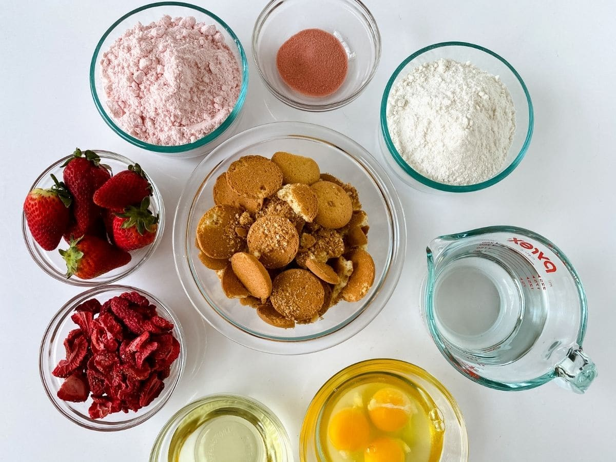 Ingredients for strawberry crunch cake in glass bowls on table