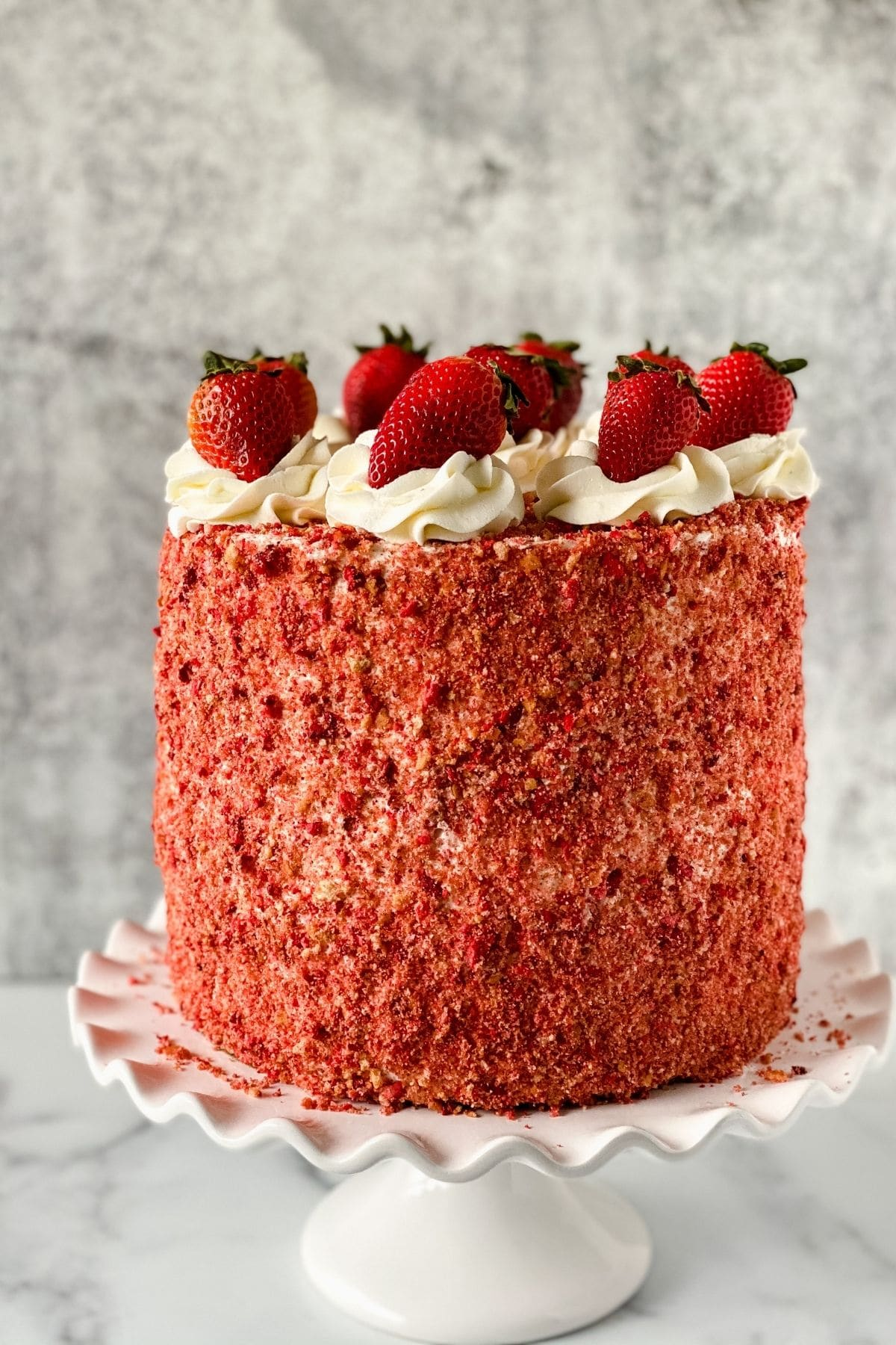 Pink cake with whipped cream and strawberry topping