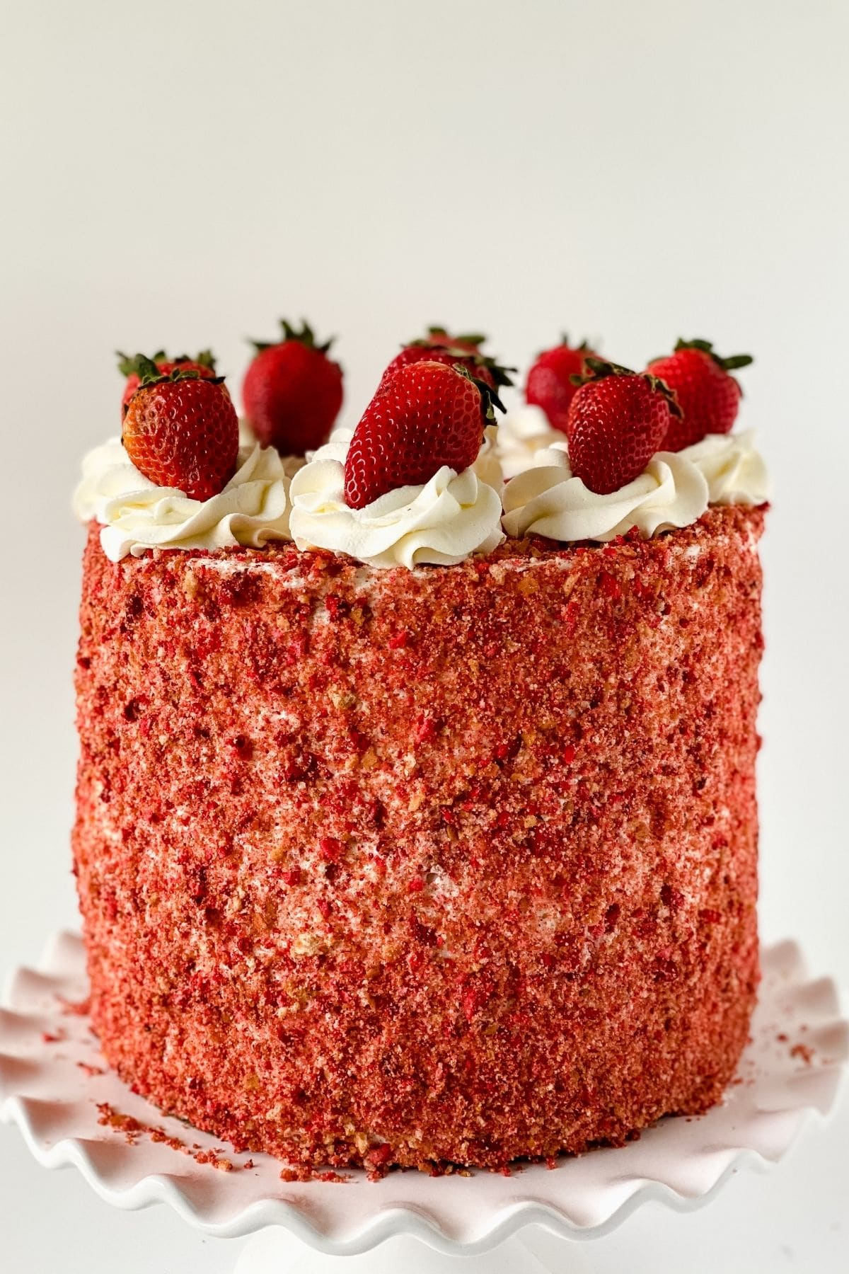 Strawberry crunch cake on white cake stand with berries on top
