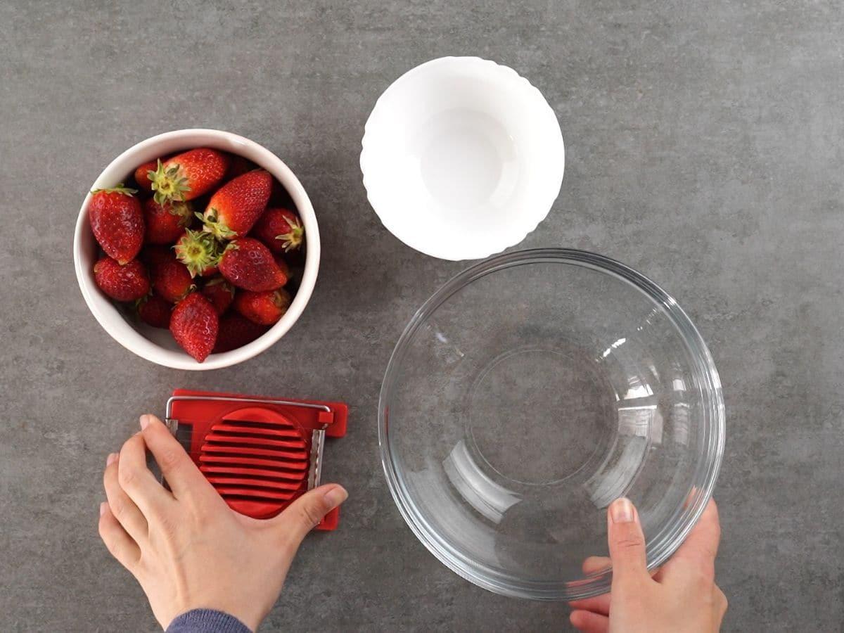 glass bowl, strawberries, slicer, and white bowl