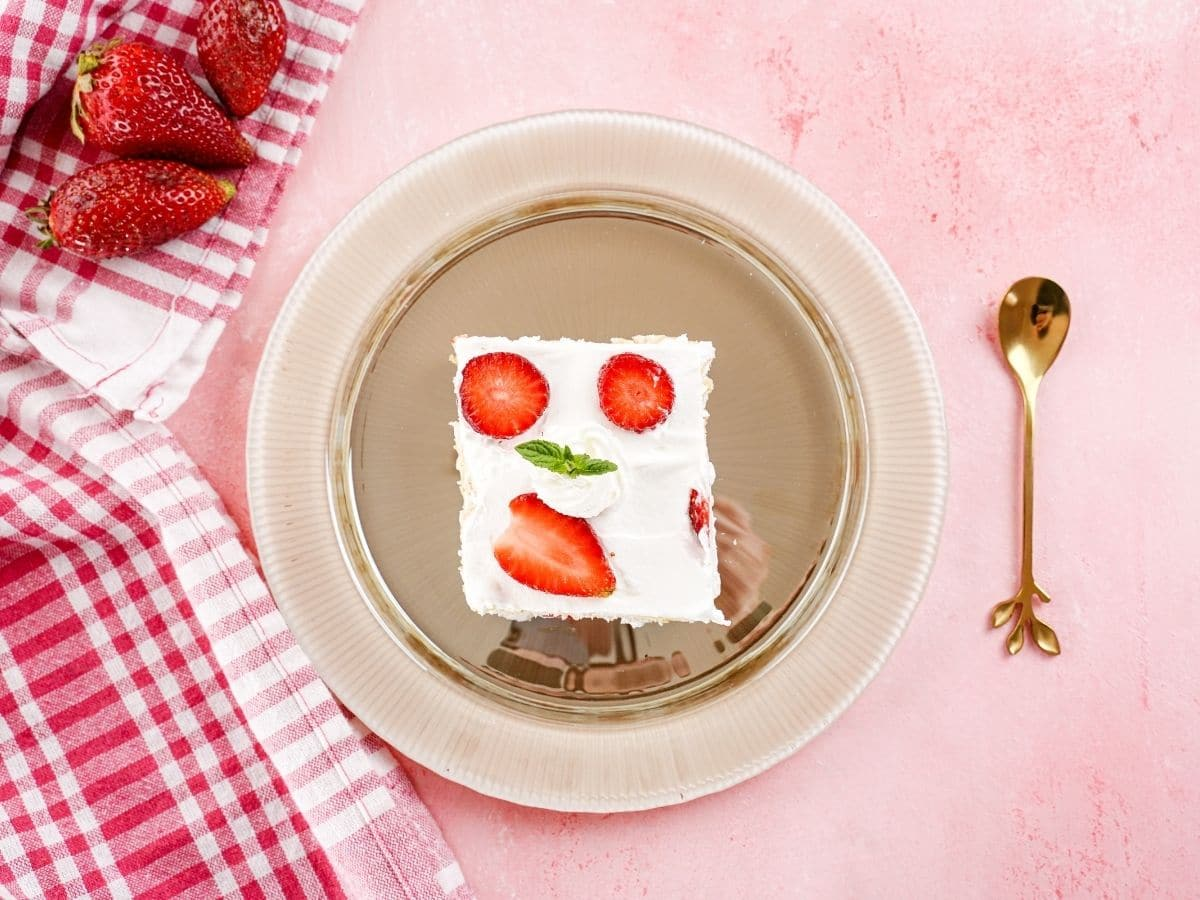 Overhead picture of tan plate with slice of cake with strawberries mint and whipped cream topping on pink table