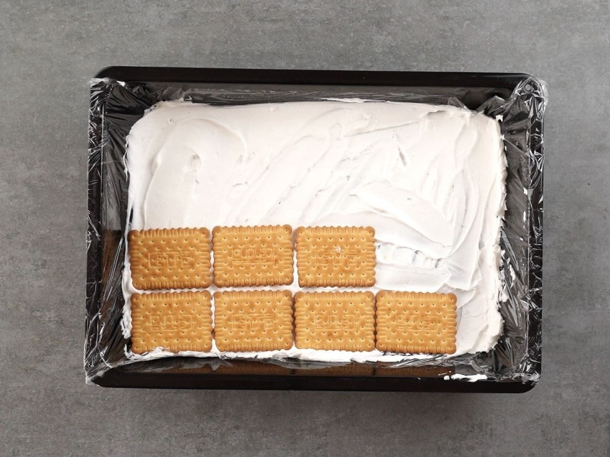 Black baking dish with whipped cream and a few graham crackers in it sitting on gray counter