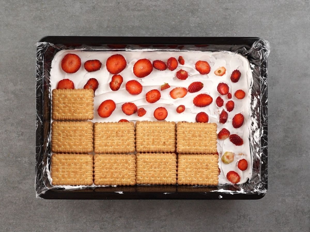 Black baking dish on gray table filled with whipped cream, layers of strawberries, and a layer of crackers