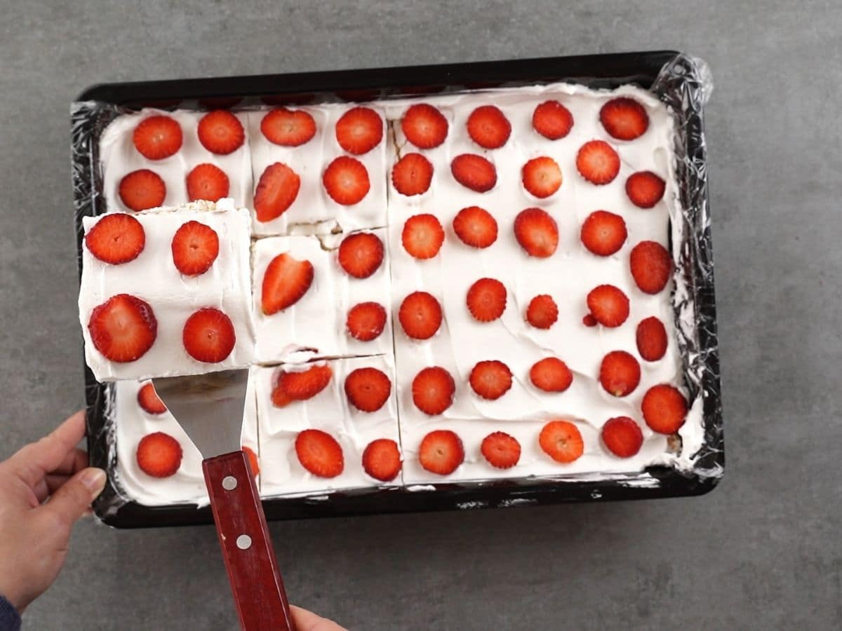 A serving of icebox cake being lifted out of black baking dish