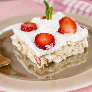 Slice of icebox cake with strawberries on brown plate next to striped red towel