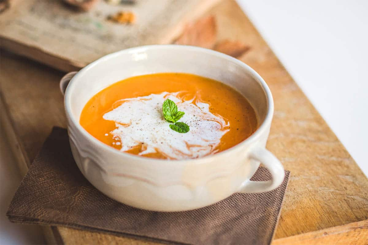 31 Pumpkin Recipes To Dig Into This Fall - classic pumpkin soup topped with cream and mint