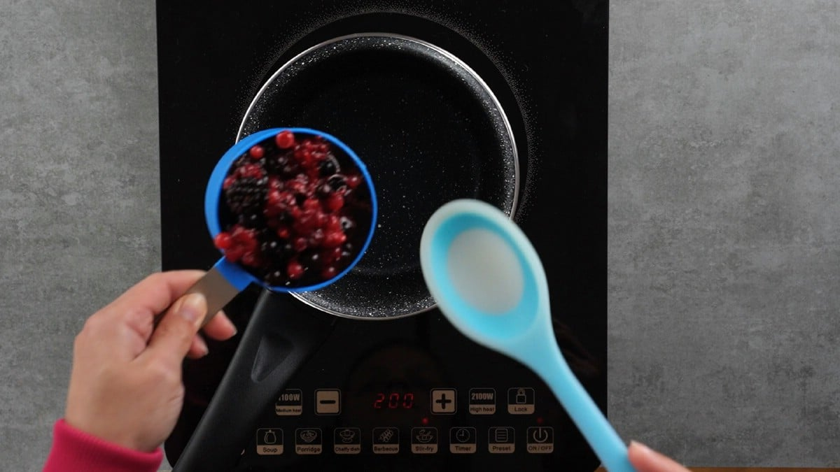 Hand pouring berries into pan by blue spoon