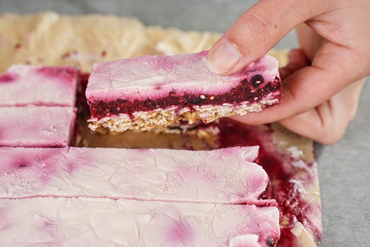 Hand picking piece of yogurt berry dessert out of pan
