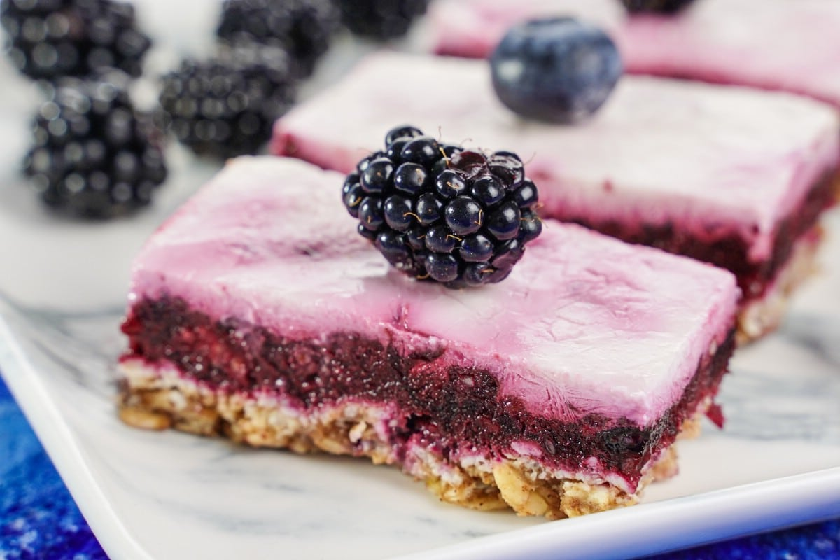 Blackberry and blueberry on white plate with dessert bars