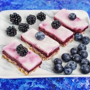 Marble platter on blue table topped with yogurt bars and blueberries