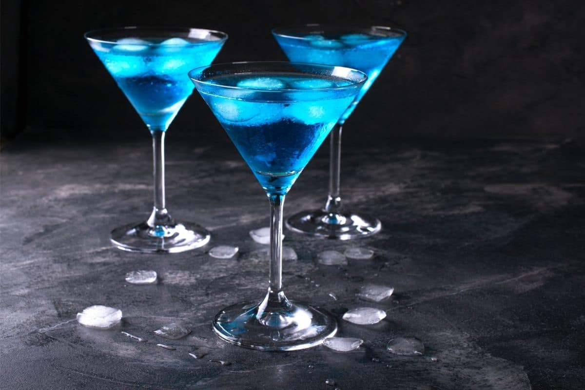Blue drink in martini glasses on black counter