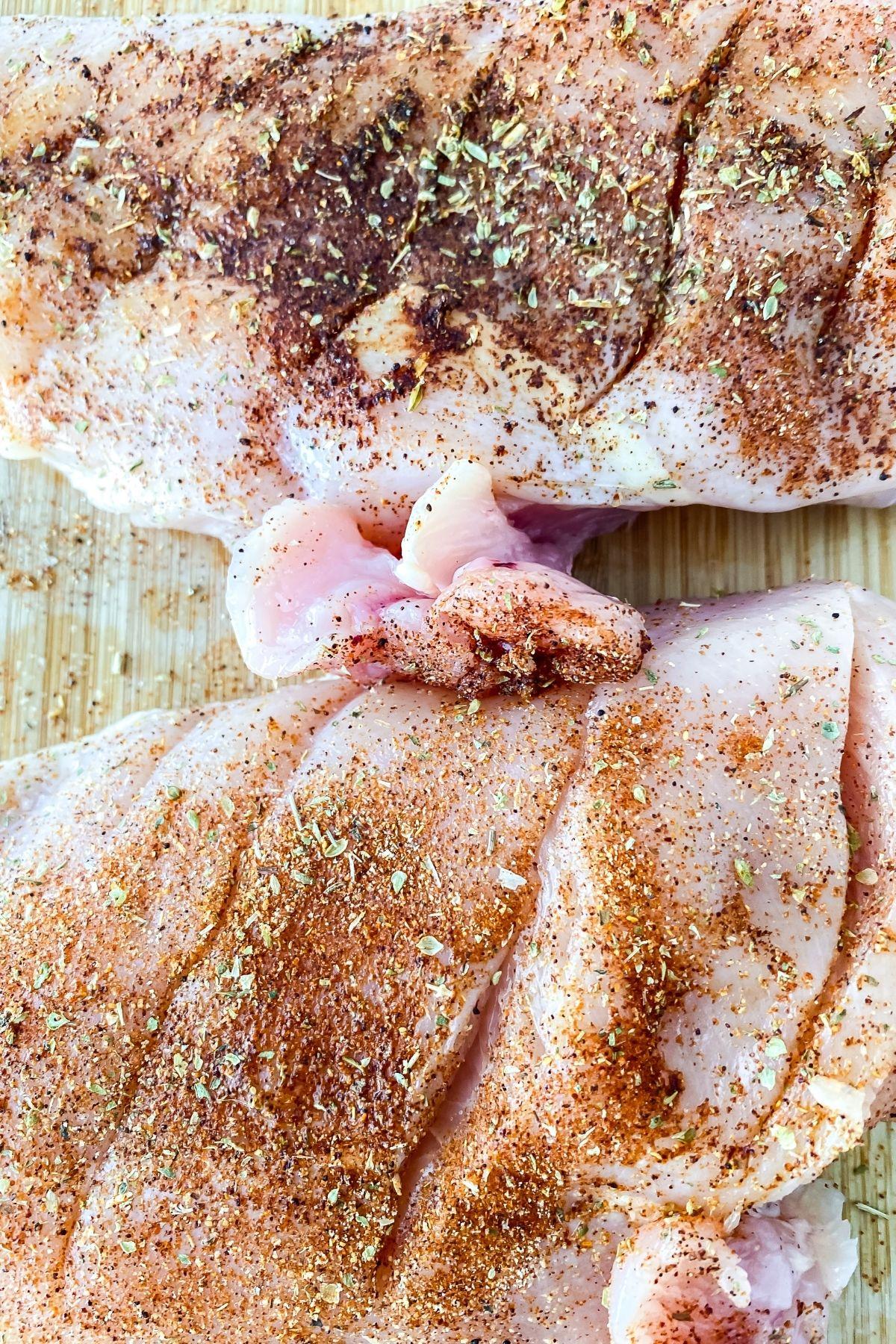 Seasoned chicken breast on cutting board