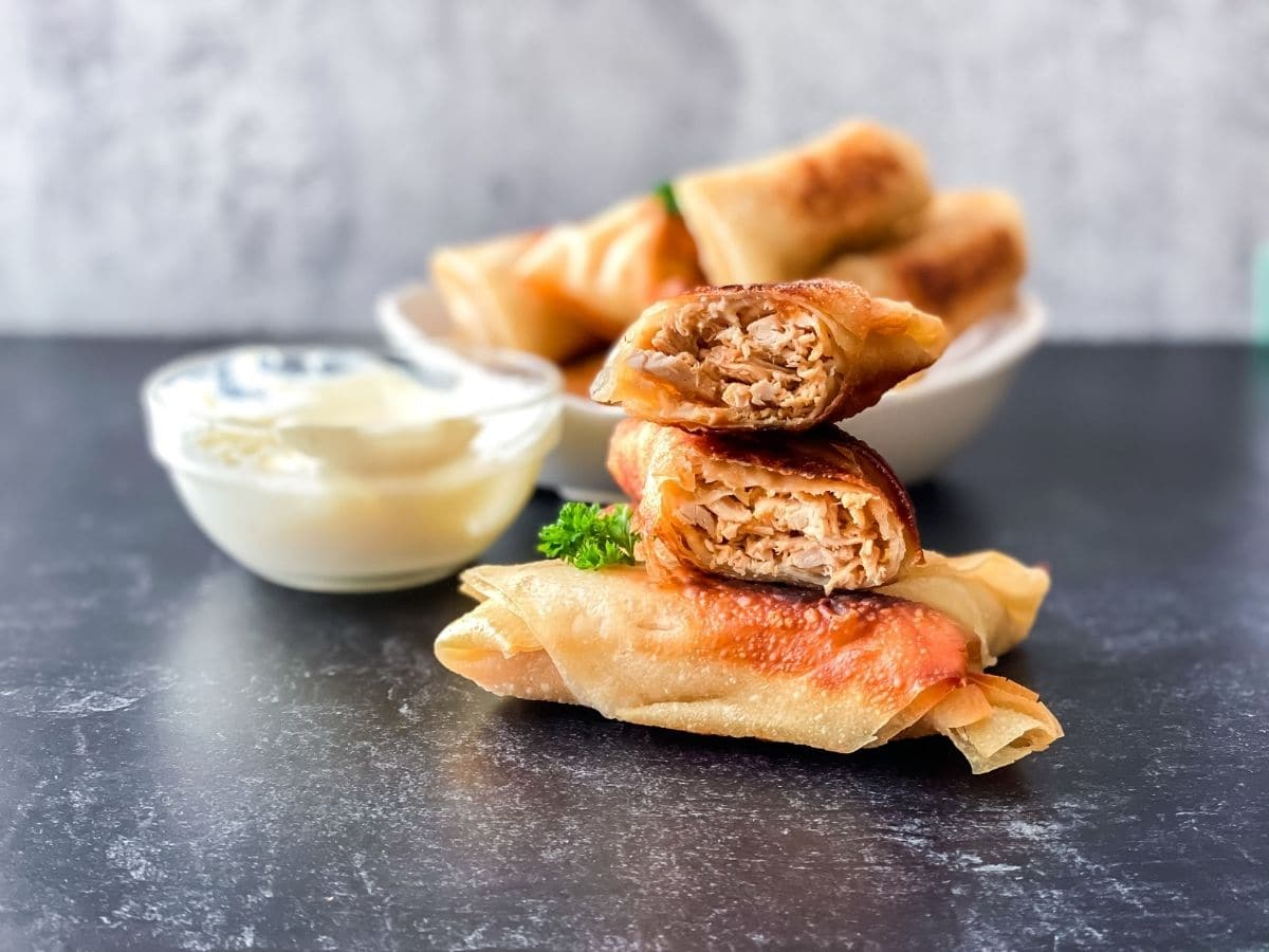 Gray table with stack of egg rolls in front and white bowl of egg rolls in back