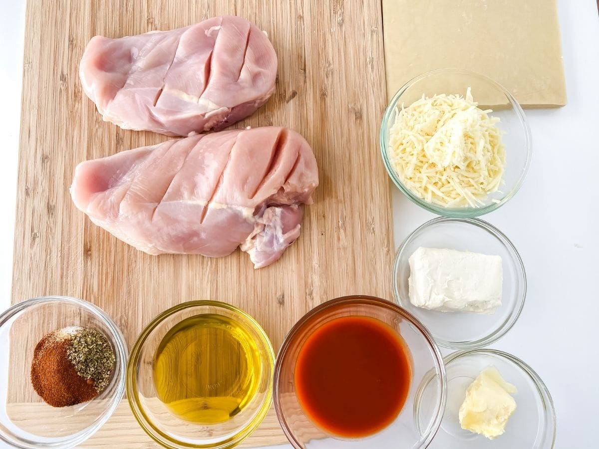 Ingredients for buffalo chicken eggrolls on cutting board and in glass bowls