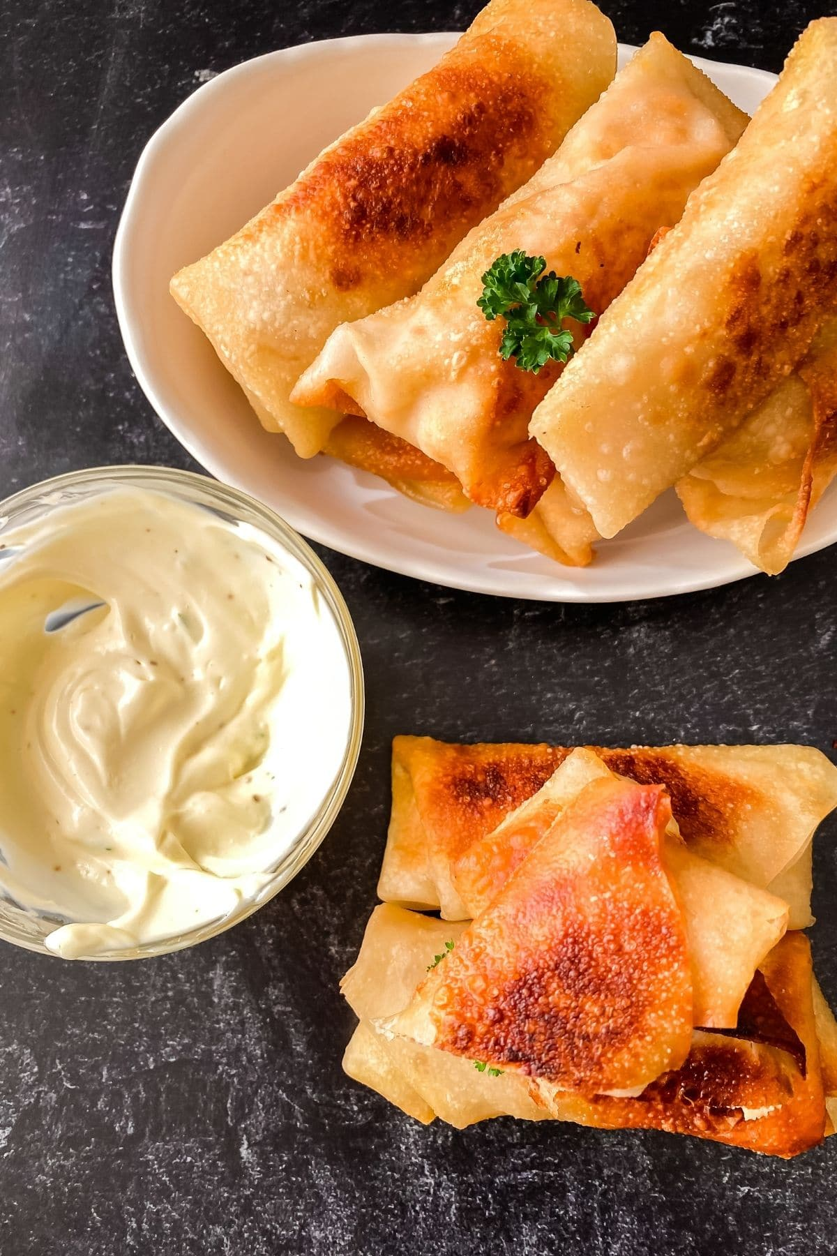 Image looking down on white plate of egg rolls with small stack on gray table beside bowl of ranch dip