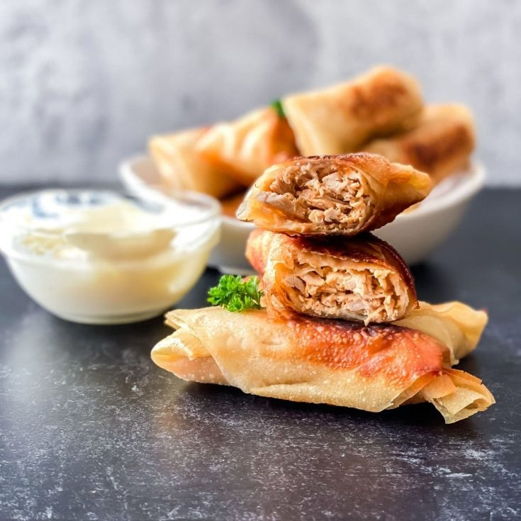 Stack of eggrolls on gray table next to bowl of ranch dip