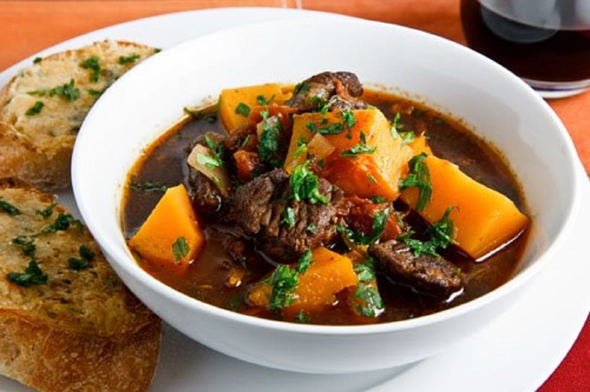 Butternut and Beef Stew topped with chopped oregano in a bowl