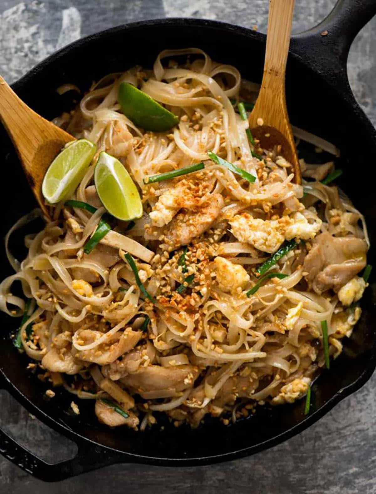 Chicken Pad Thai with lemon wedges in a cast iron skillet